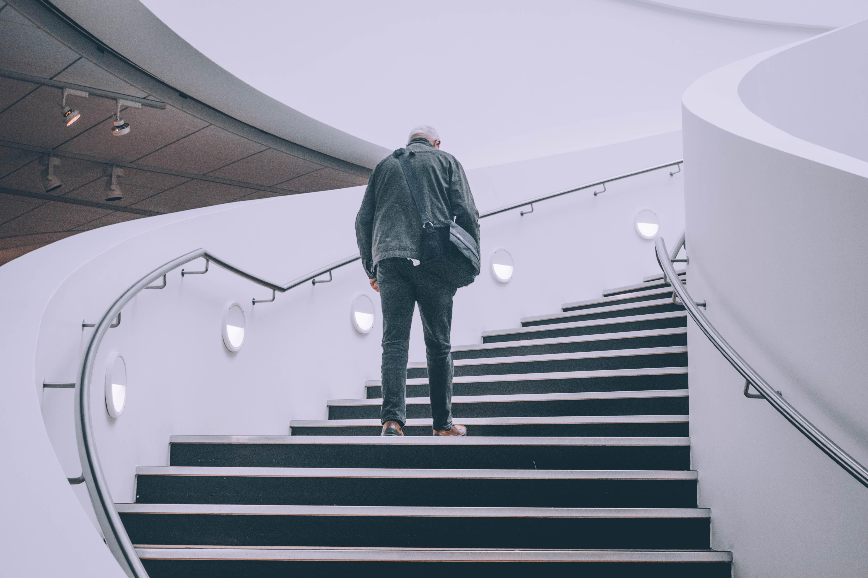 man wearing black jacket standing on black concrete stairs