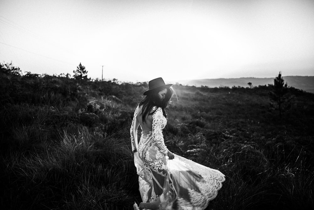 grayscale photo of woman in dress standing on grass field
