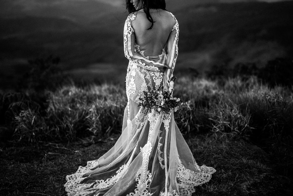 grayscale photo of woman wearing wedding dress holding bouquet of flower