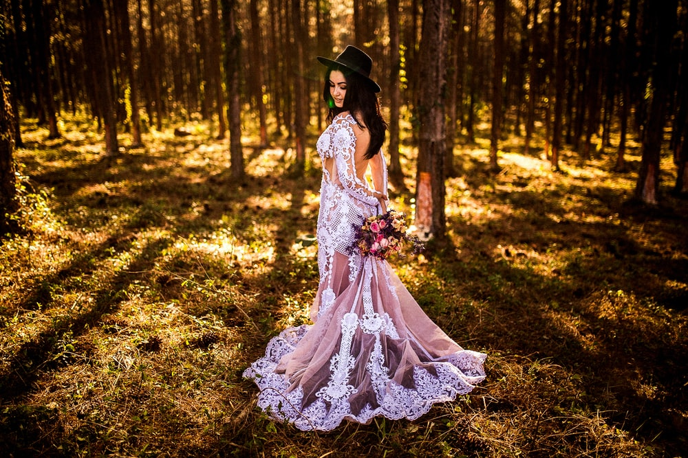 woman wearing white and grey lace dress standing in forest during daytime