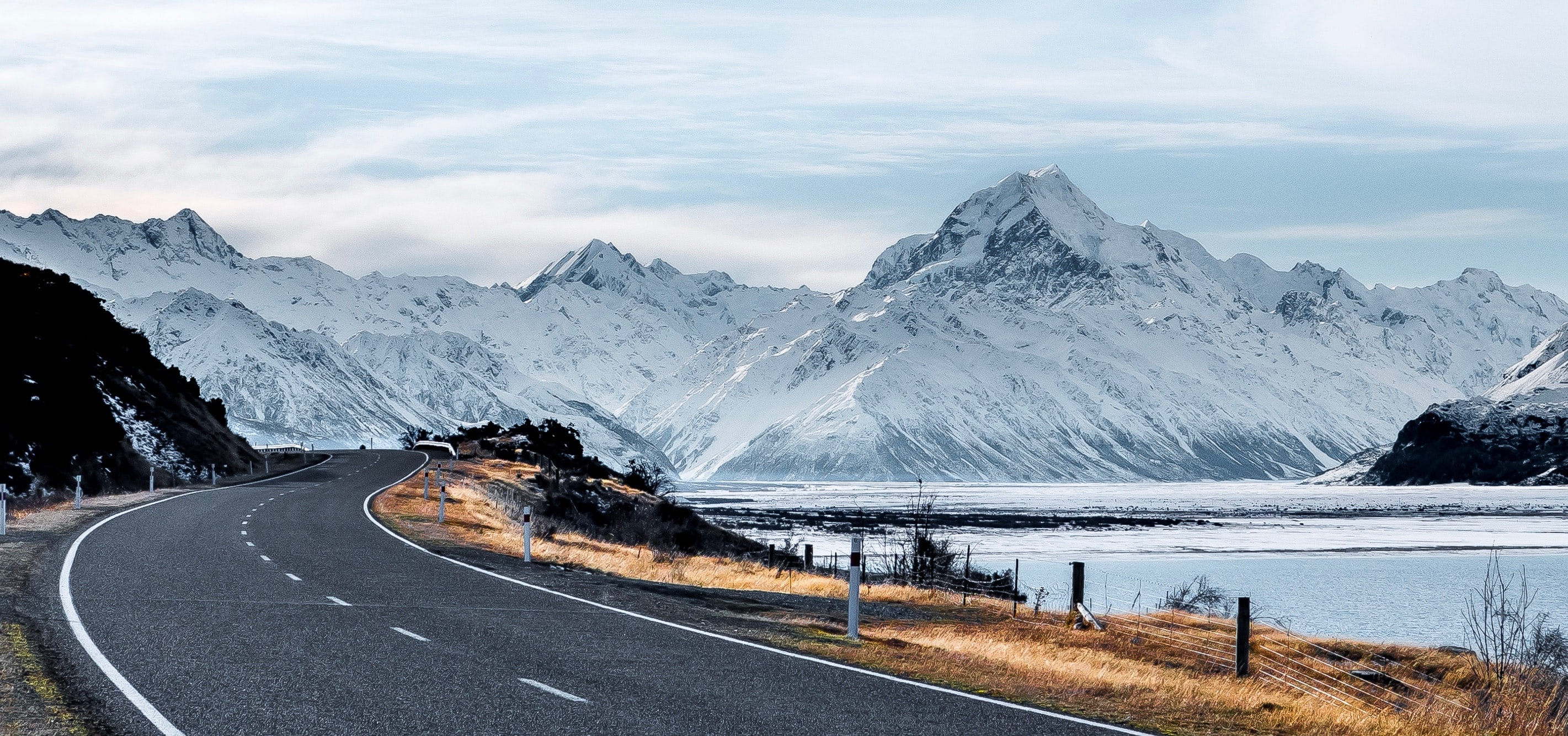 gray road beside body of water fronting mountain