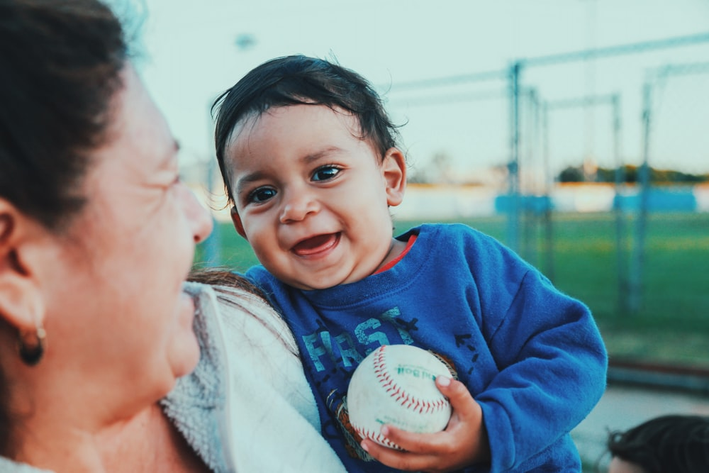selective focus photo of baby holding baseball