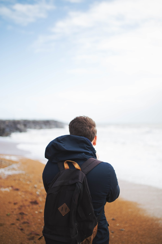 man wearing blue hooded jacket standing near the sea