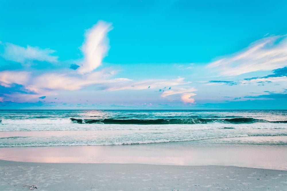 seashore under blue cloudy sky
