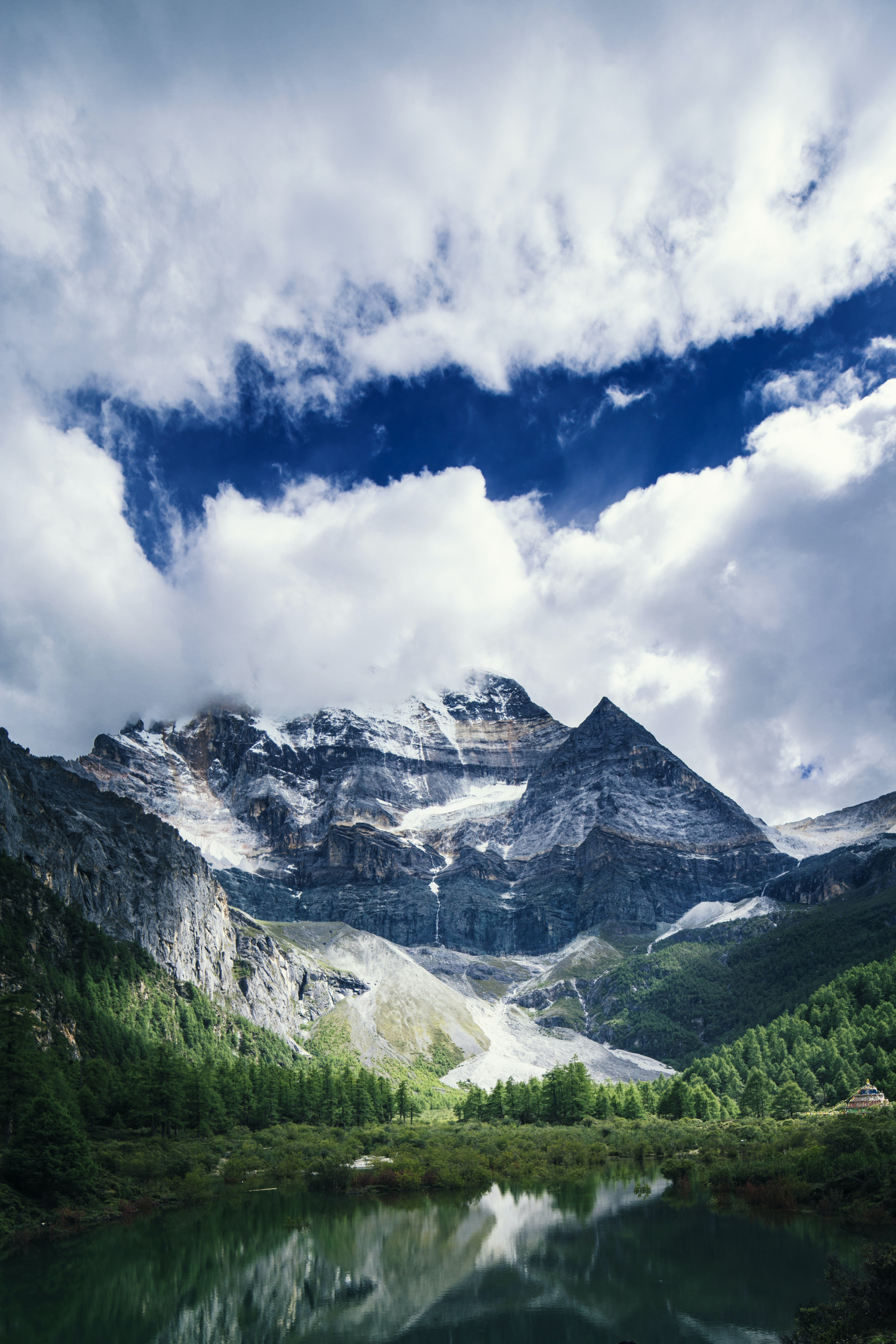 landscape photography of mountains, plants, and river under clouds