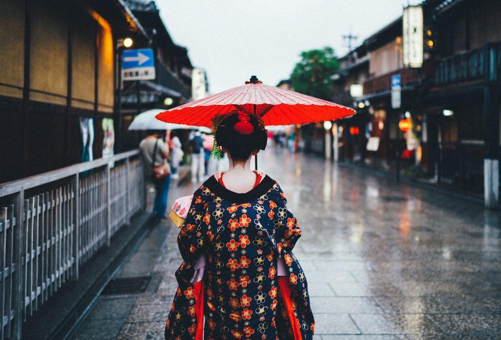 woman holding oil umbrella near on buildings