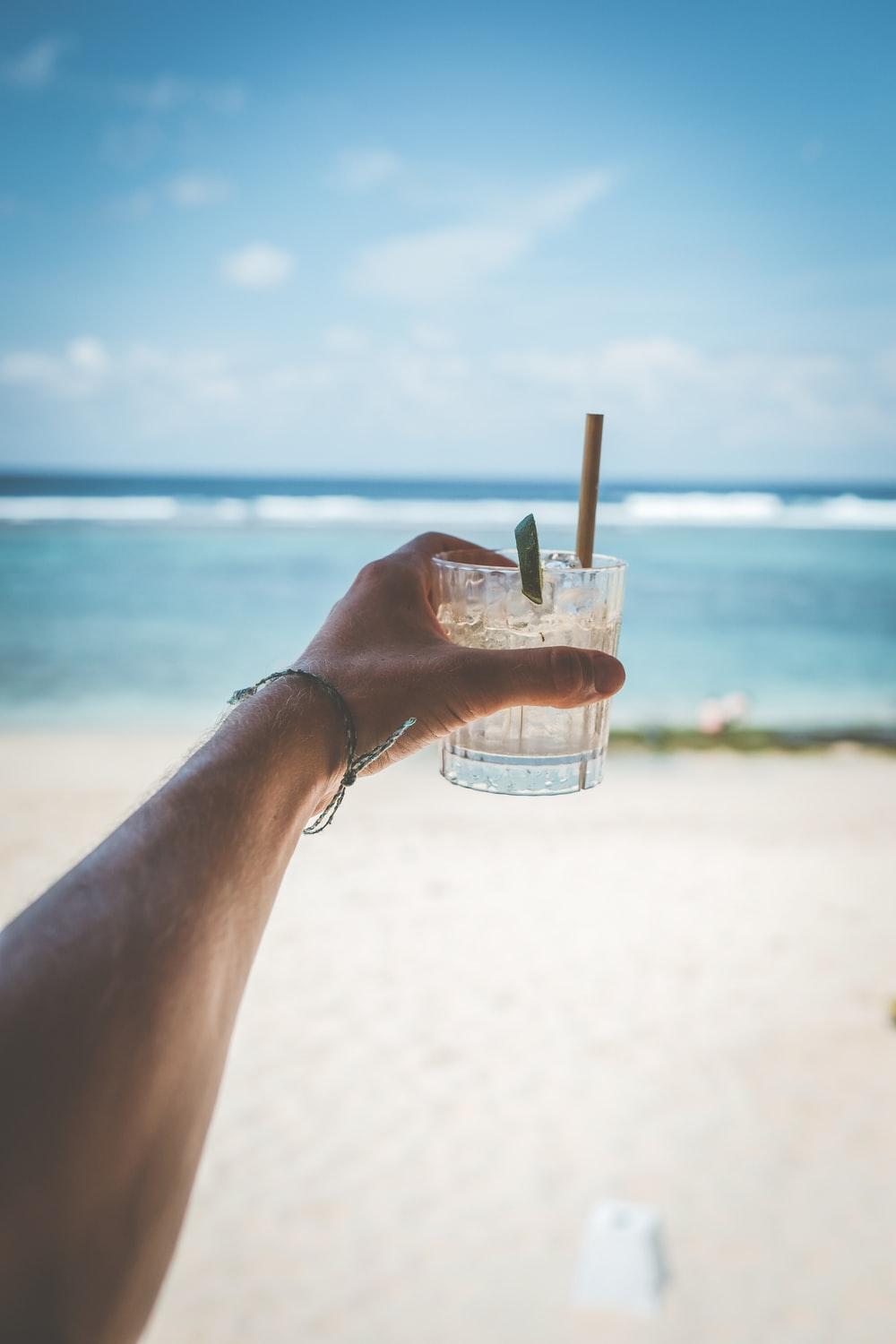 person holding drinking glass filled by straw