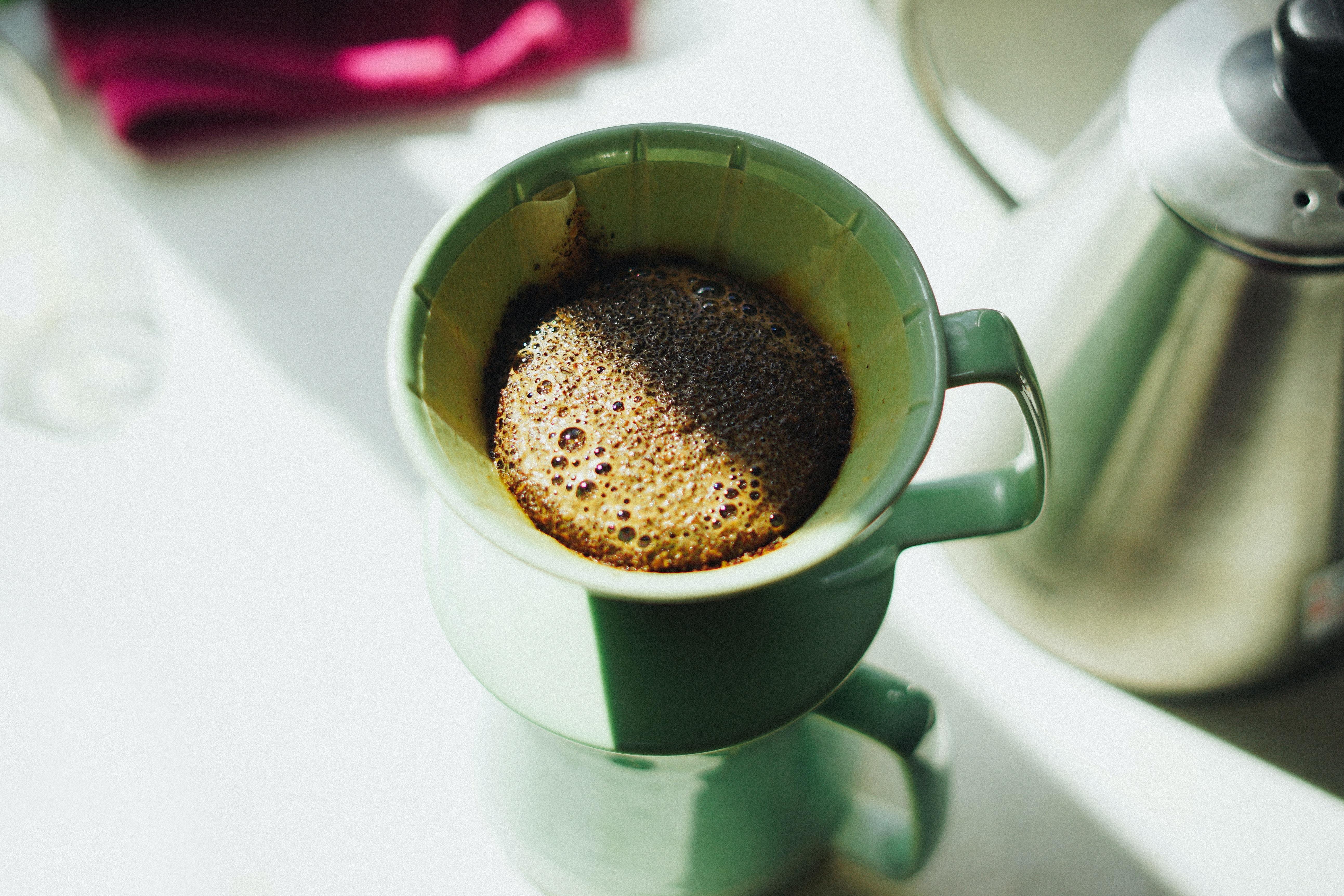 brown beverage in brown mug on white table