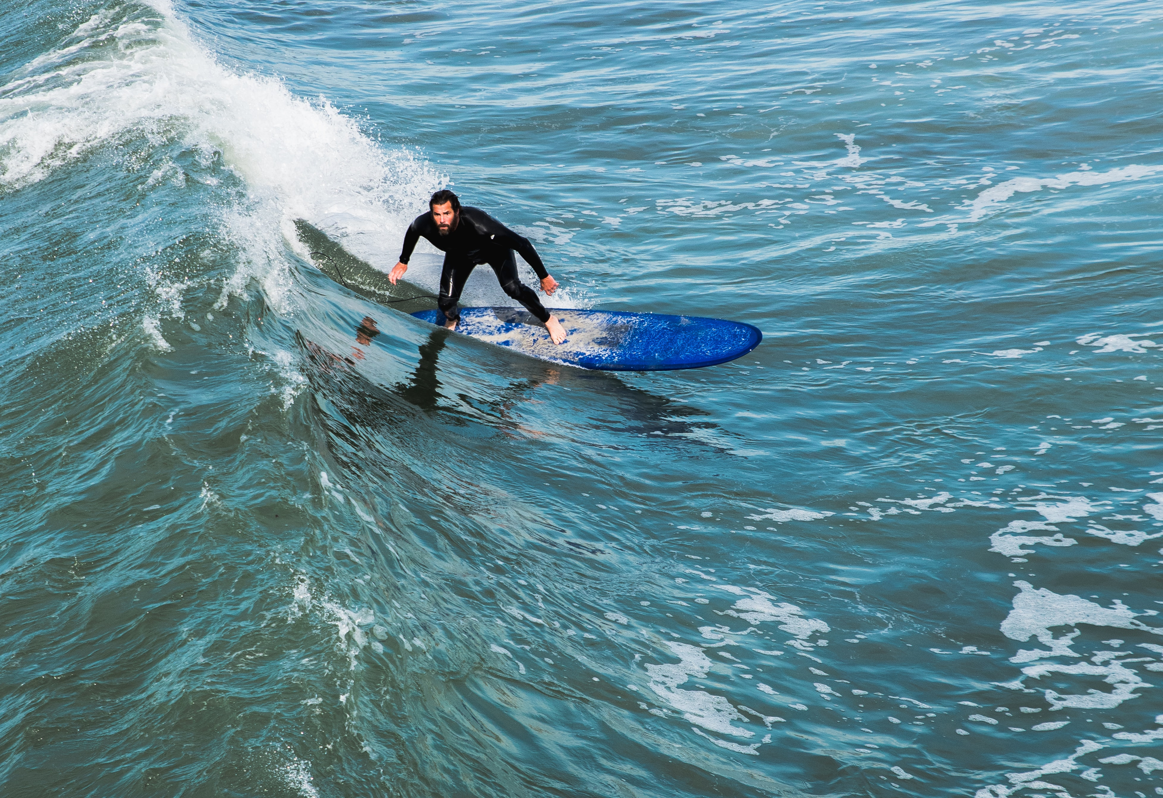 man in black wet suit surfing on wave during daytime