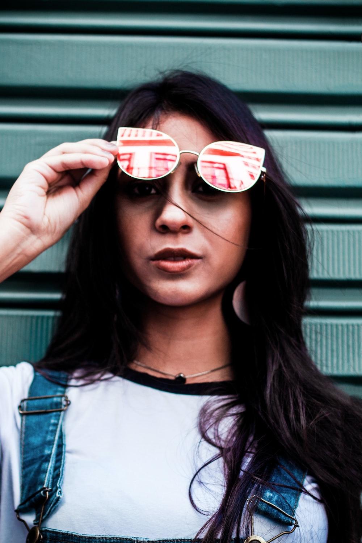 woman holding sunglasses near gray walpl