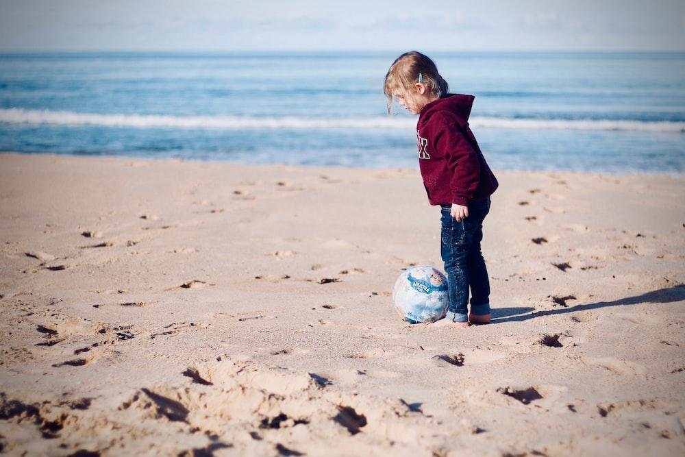 girl standing beside ball on seashore