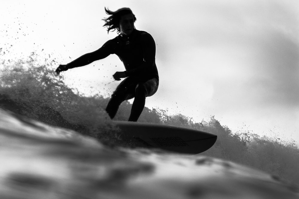 grayscale photo of man riding a surfboard