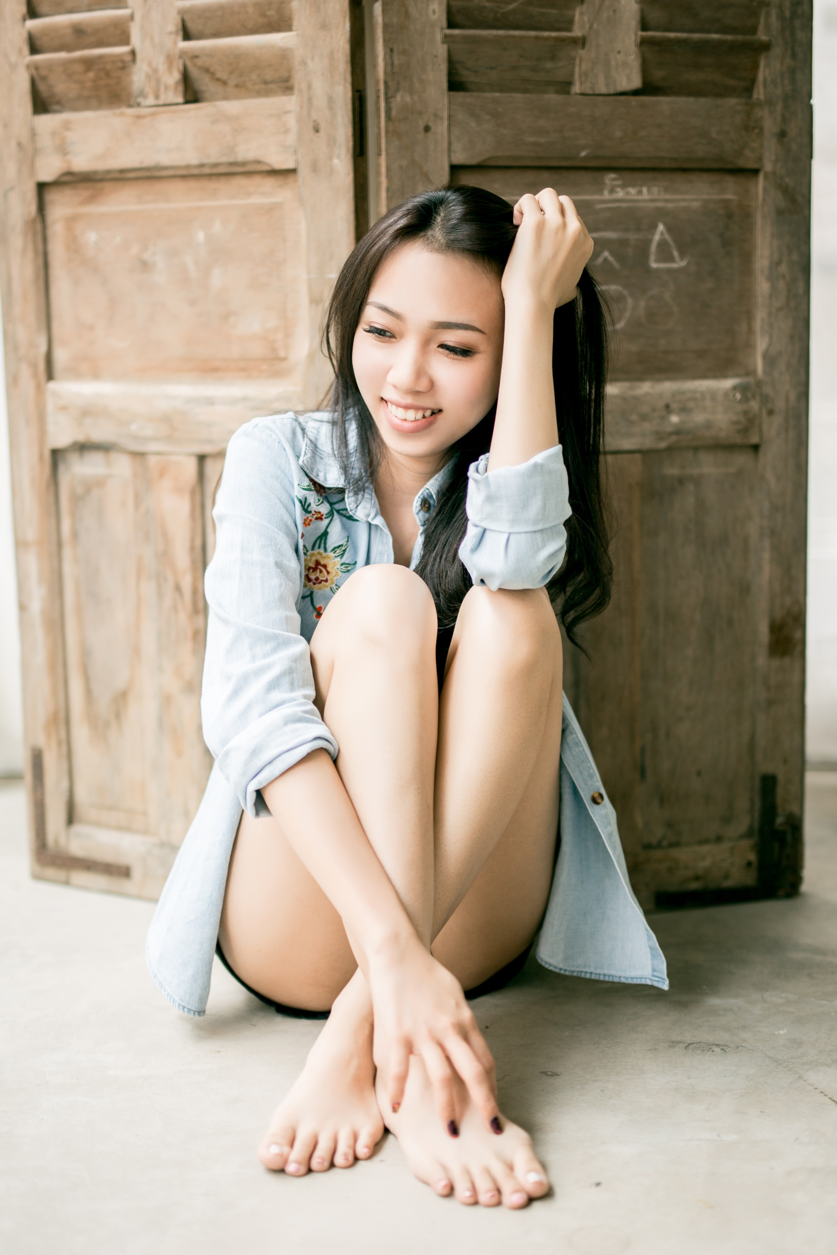 smiling woman sitting on floor back of wooden wall