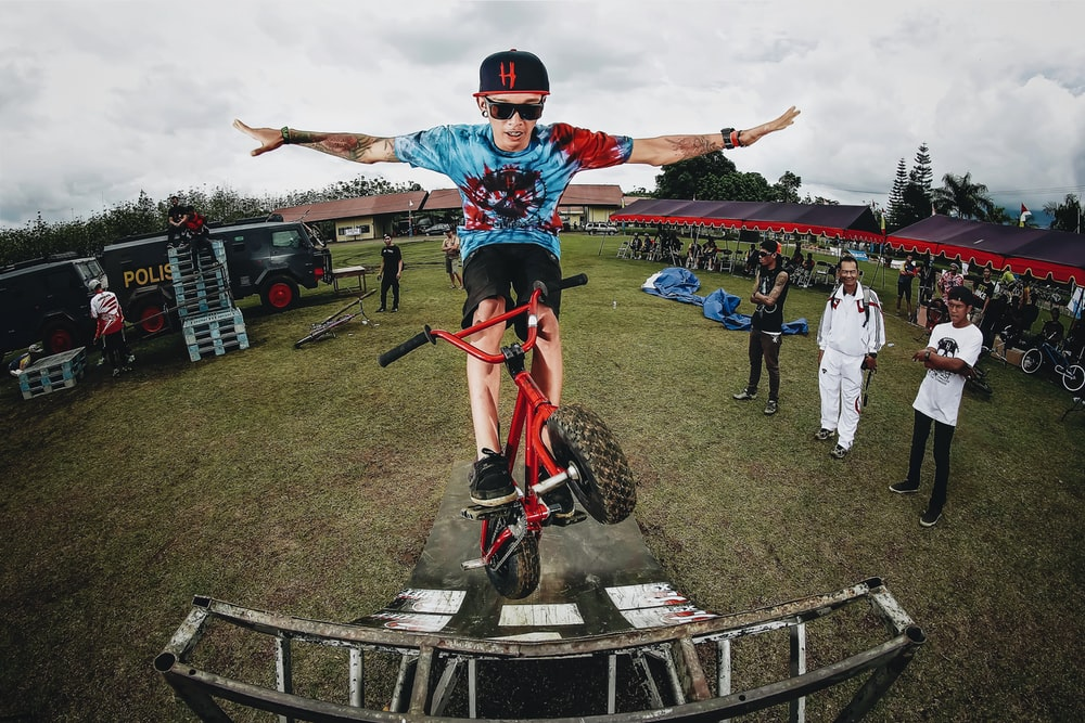 boy doing bicycle tricks in front of many people