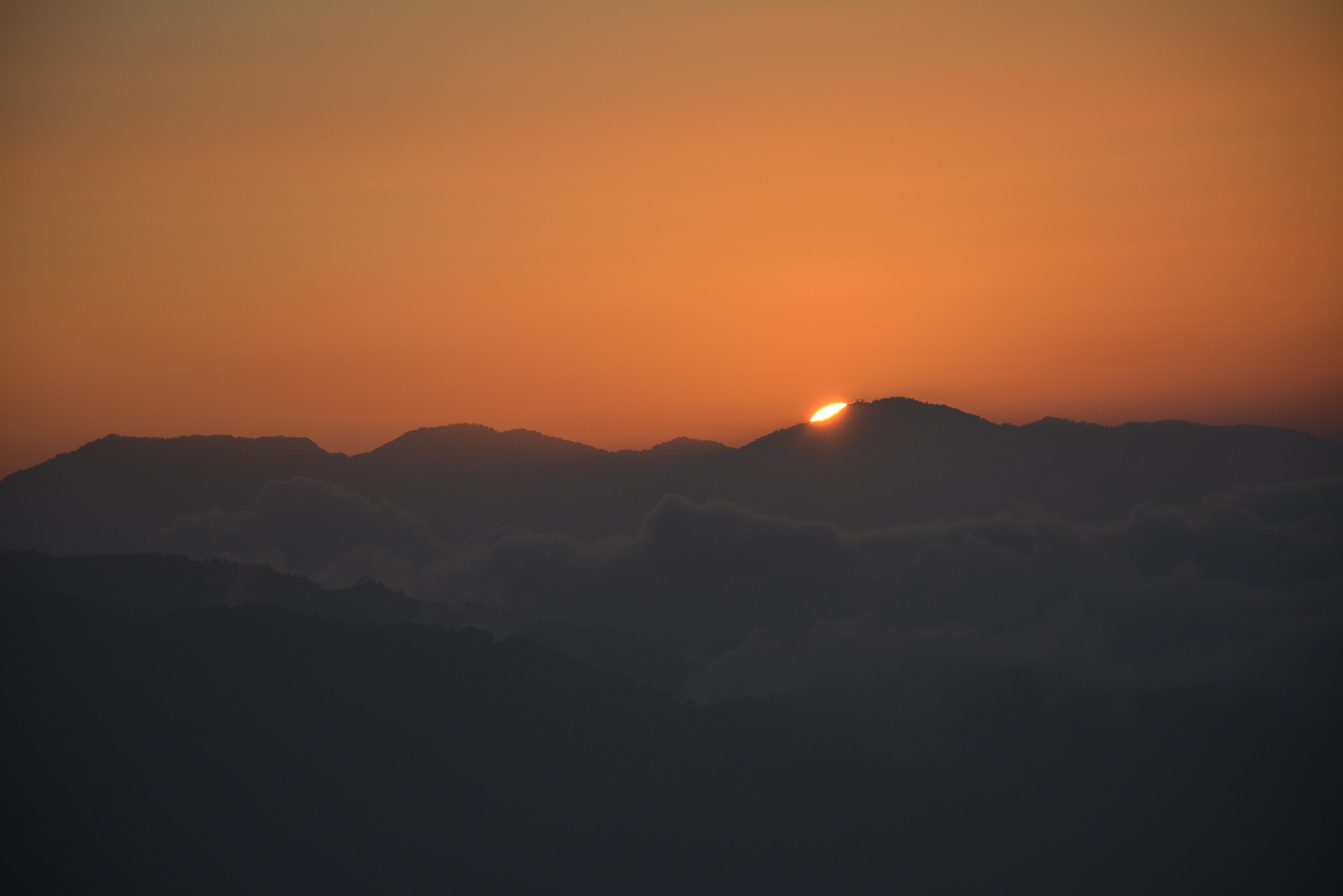 sun setting behind mountain ranges