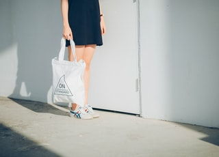 woman holding bag while standing near wall