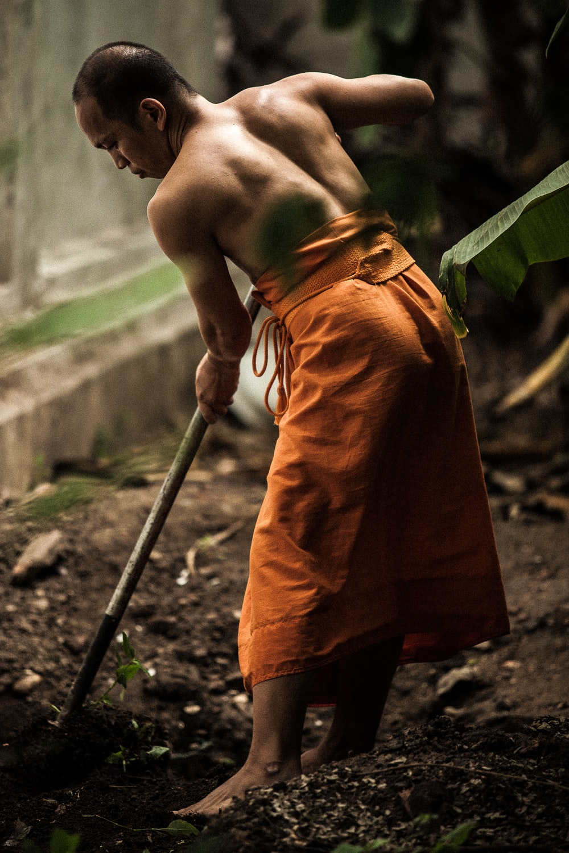 monk gardening near grey wall