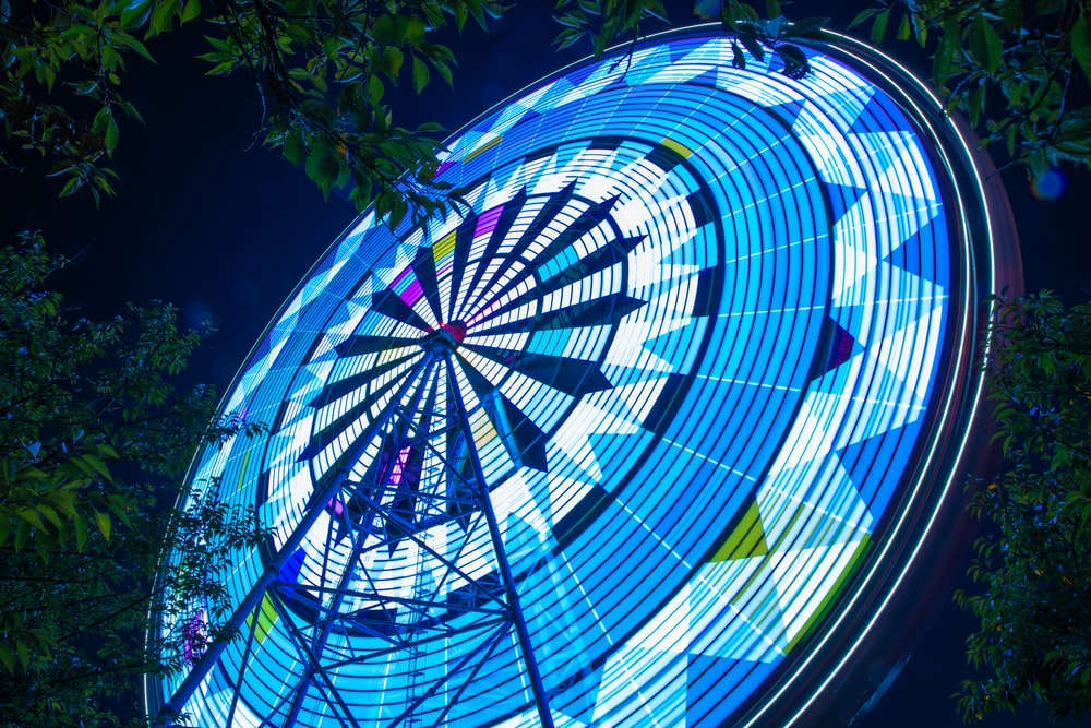 lighted Ferris wheel in low-angle photography at night