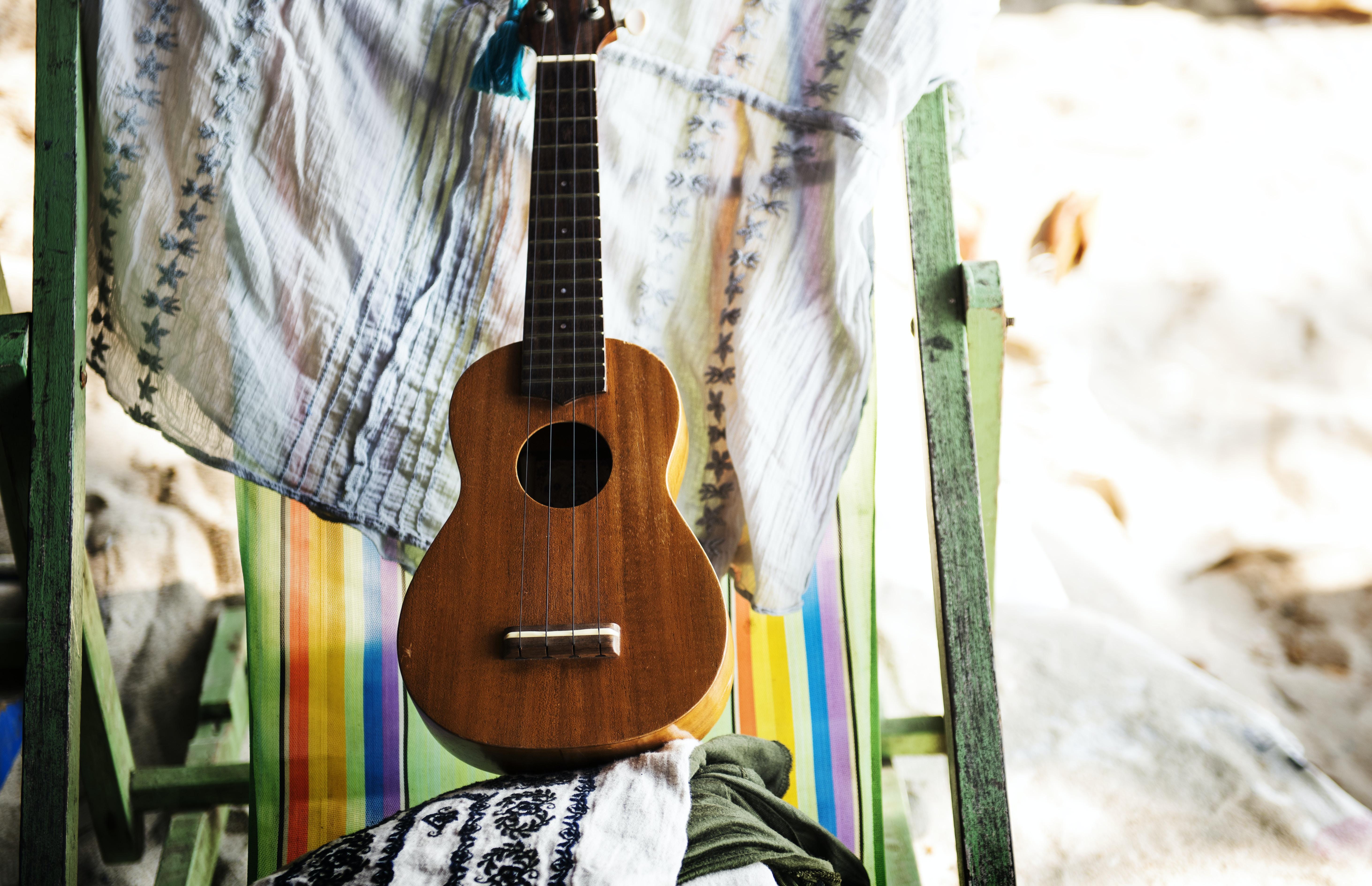 brown ukulele near beige textile