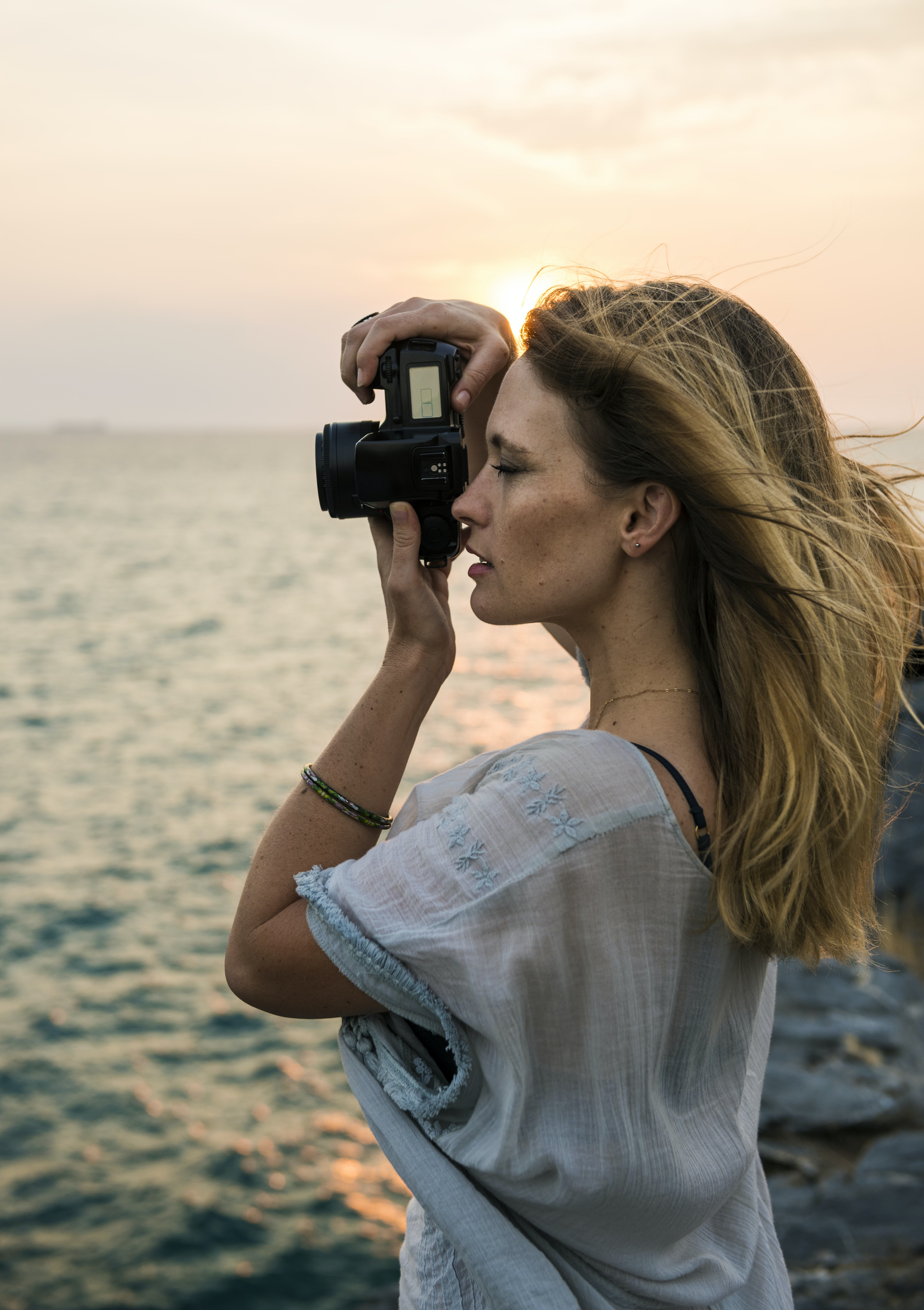 woman taking photo near body of water during daytime