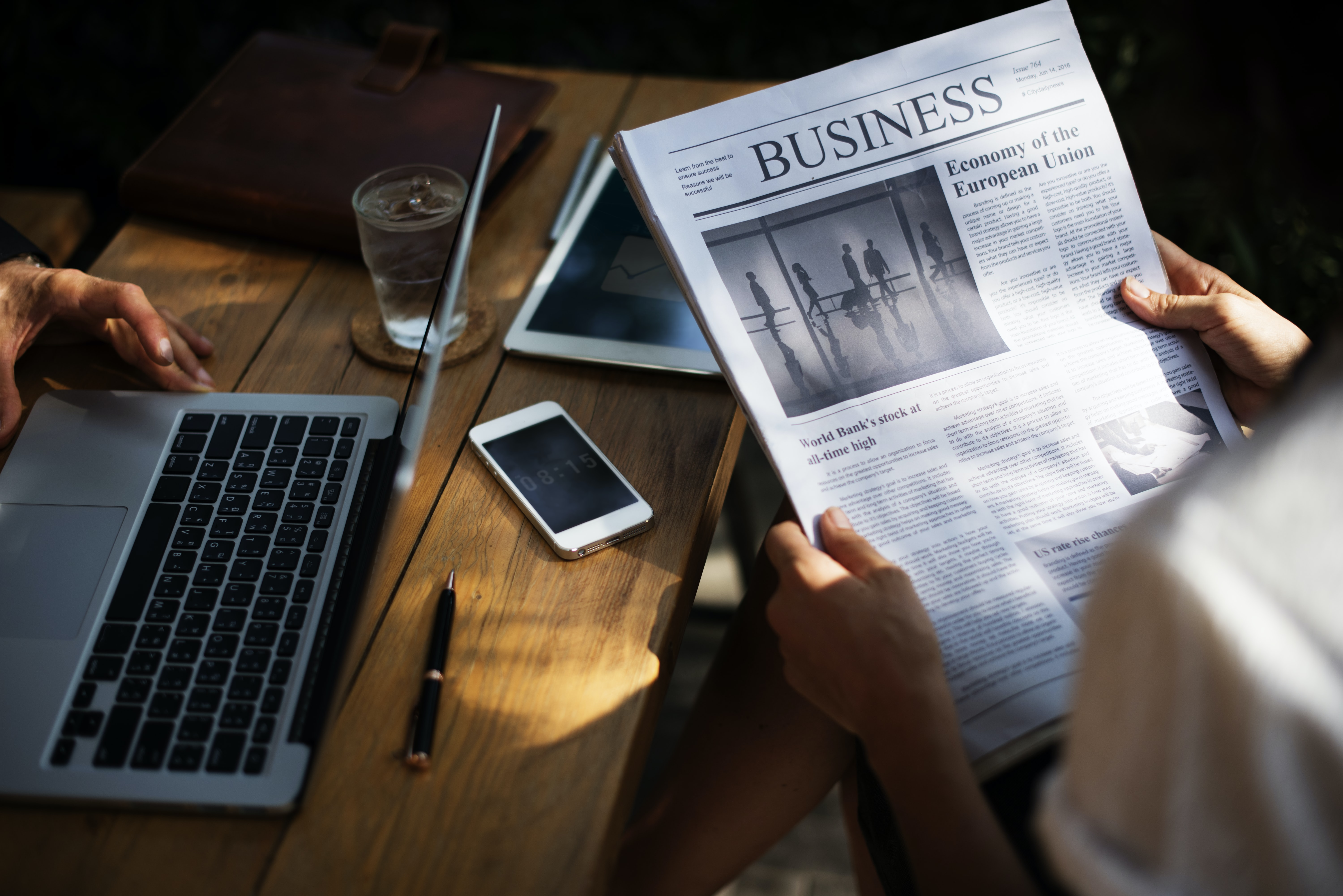 person holding Business newspaper near gray laptop