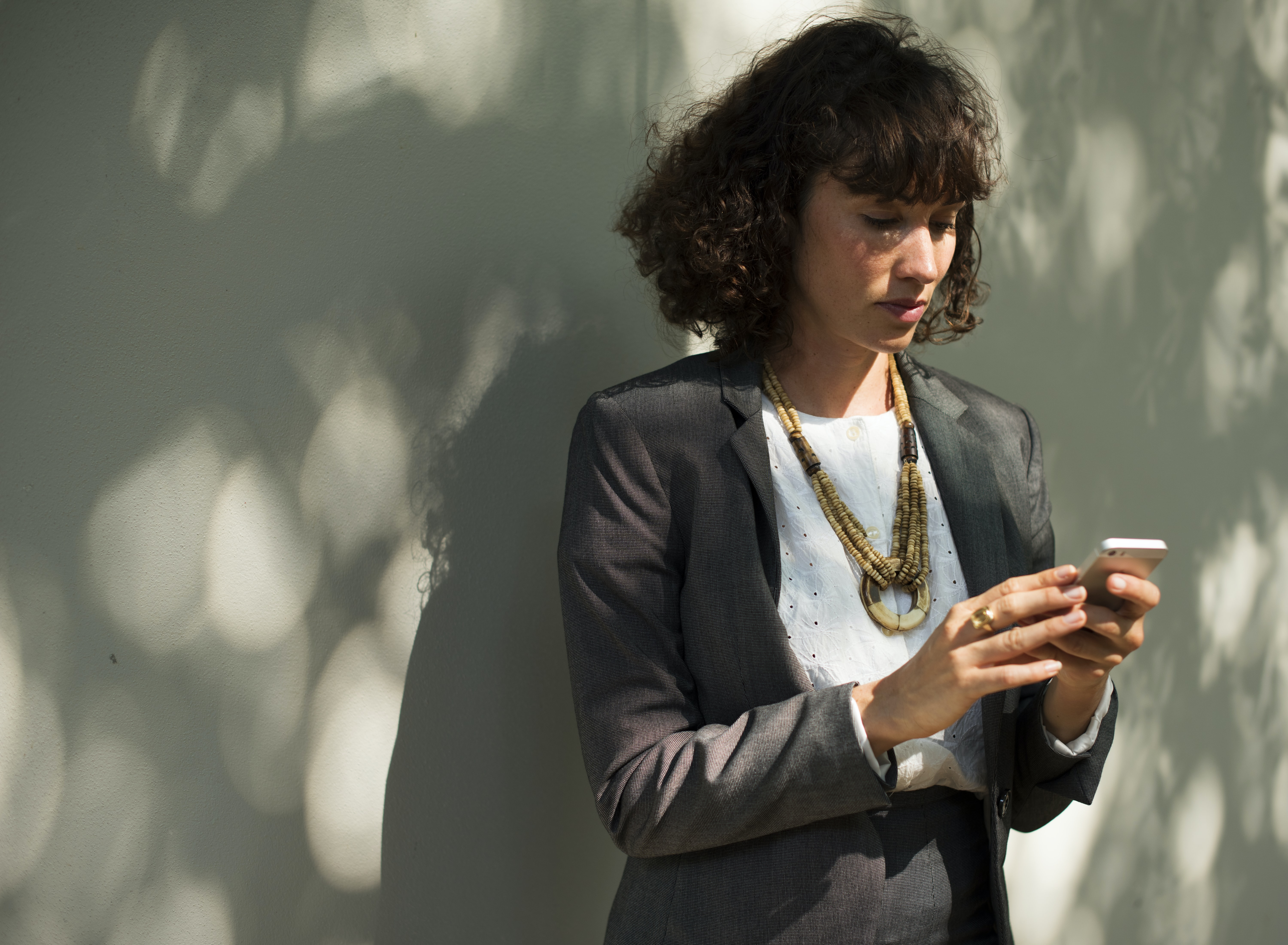 woman holding smartphone standing near wall