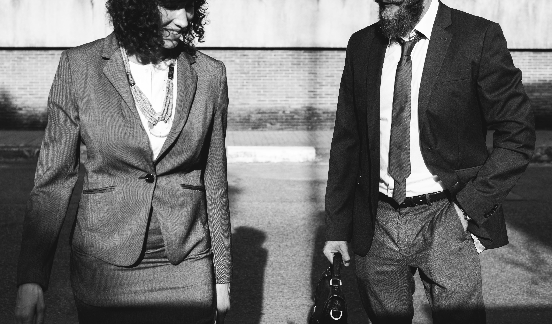 grayscale photo of man standing near woman