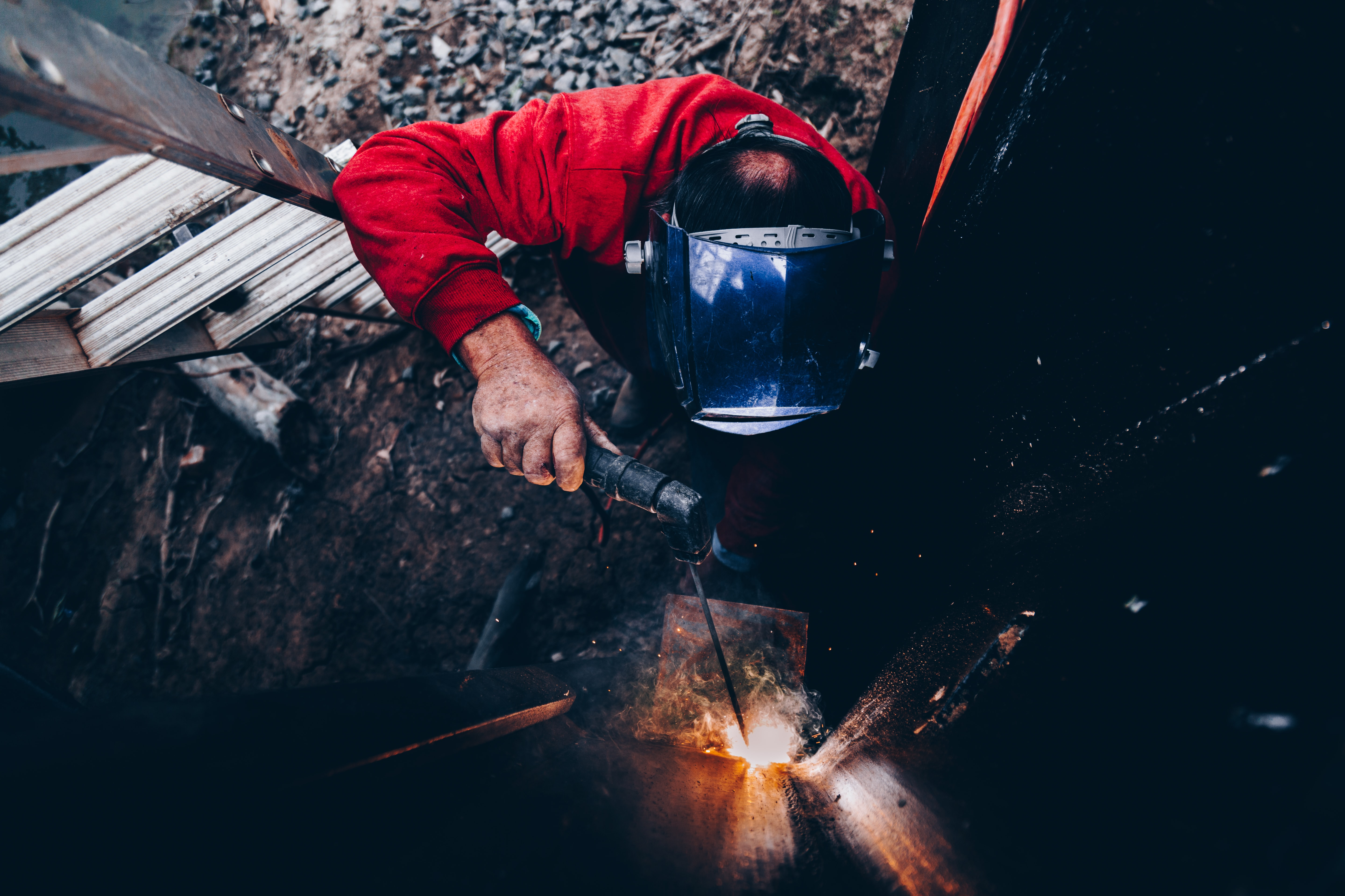 man holding welding machine and wearing welding mask