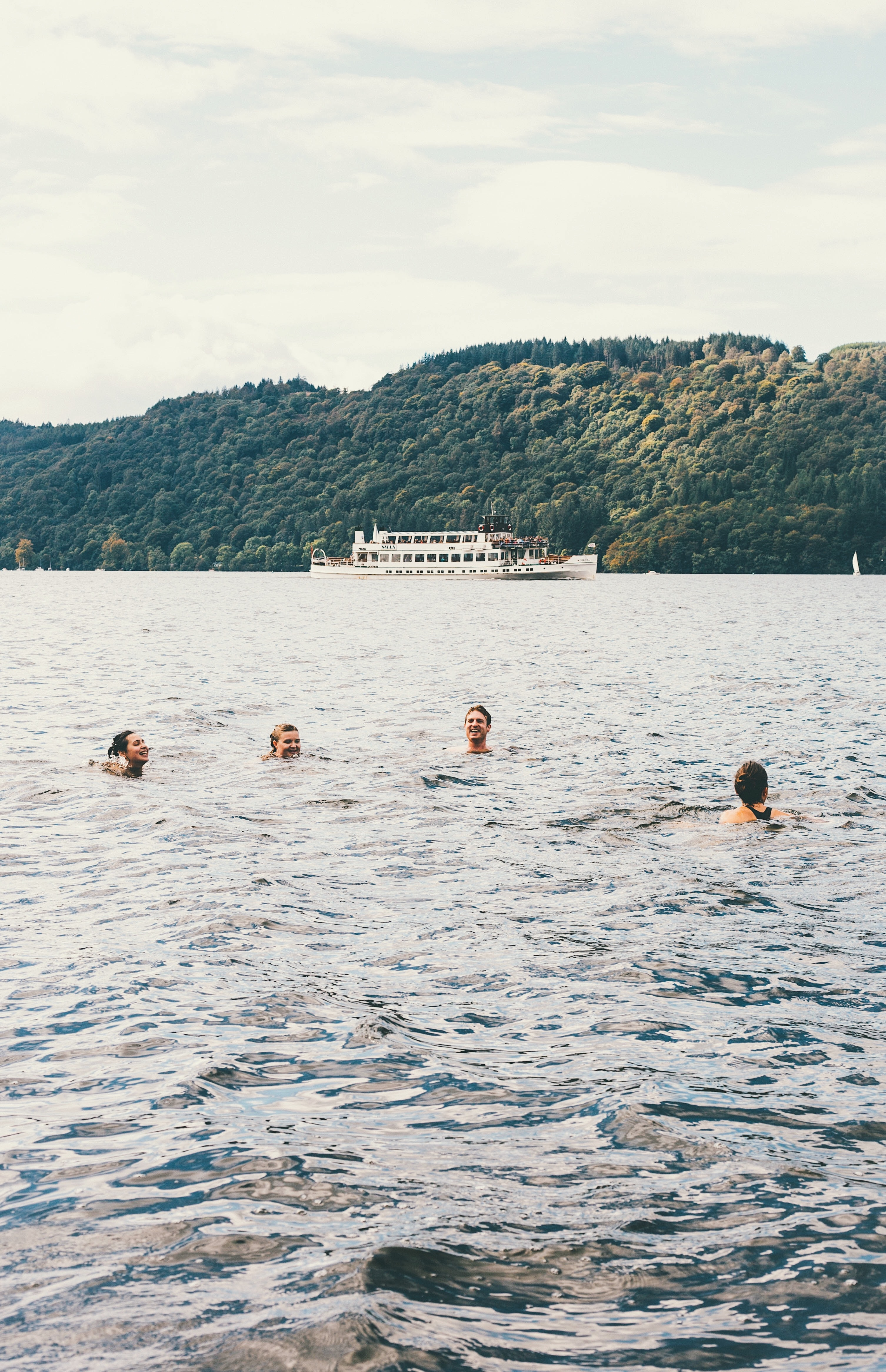 four person swimming on body of water
