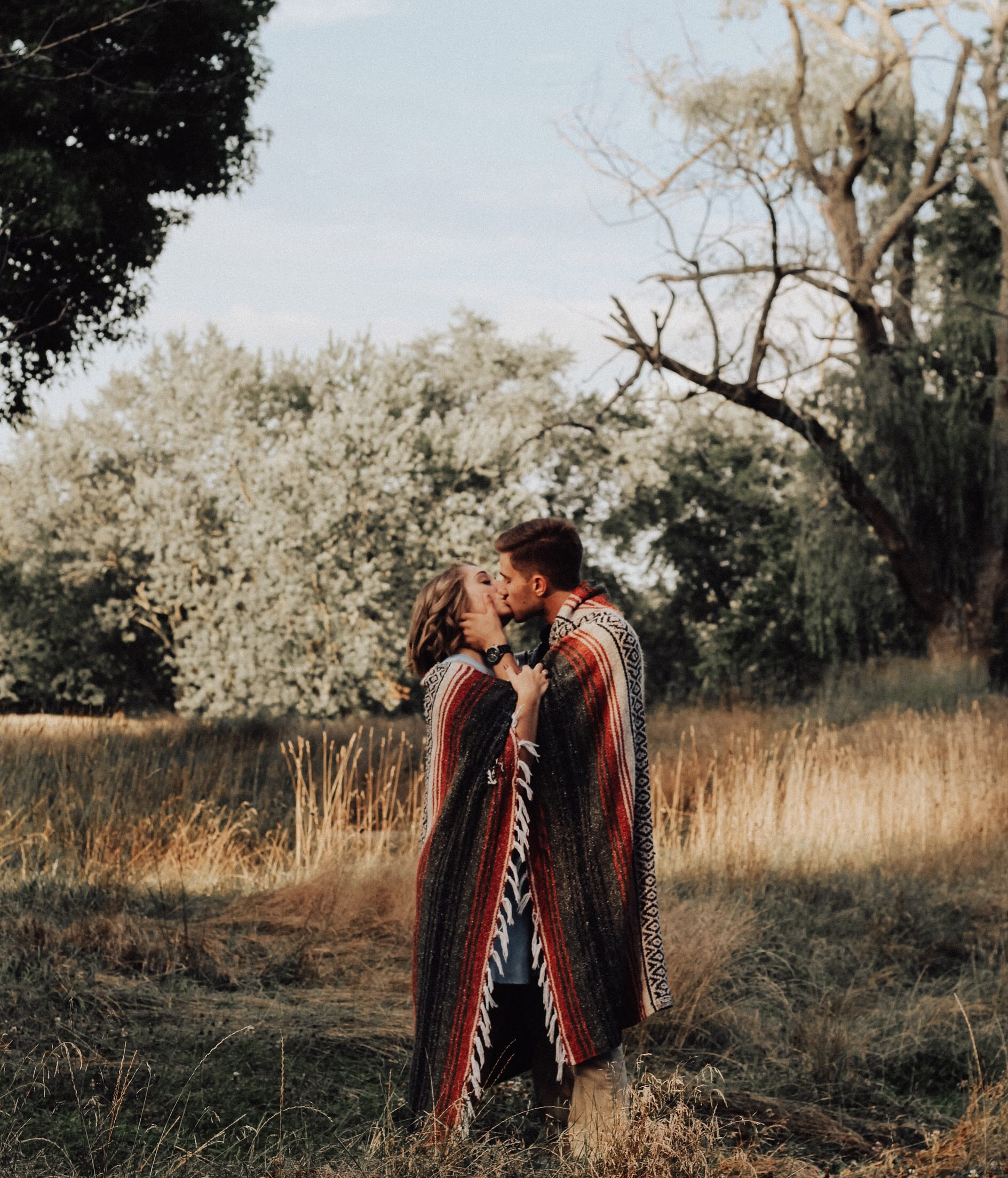 photo of man and woman kissing near brown bare tree