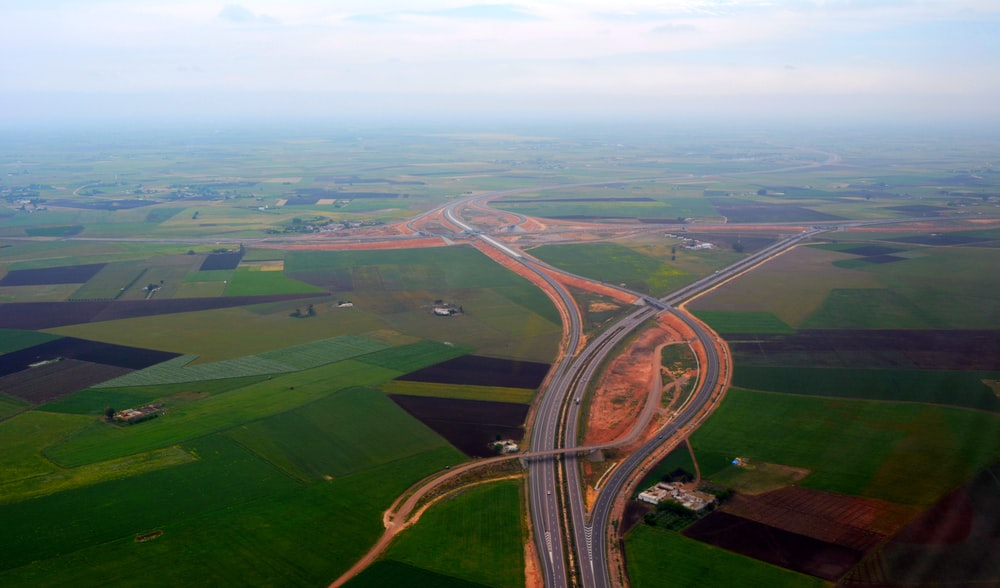 aerial view of freeway between green fields