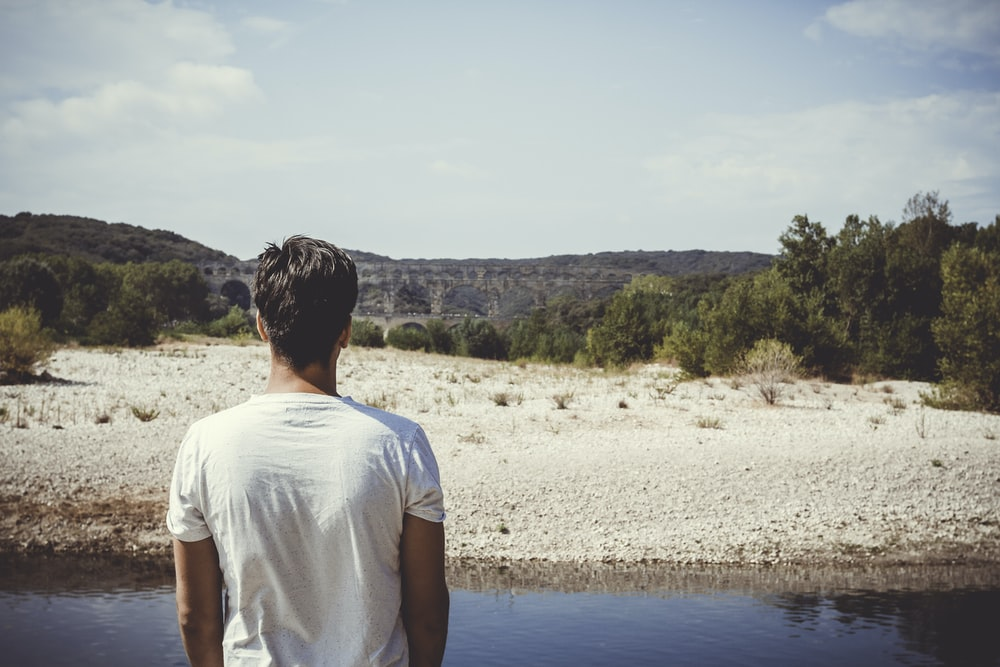 man standing on side of river