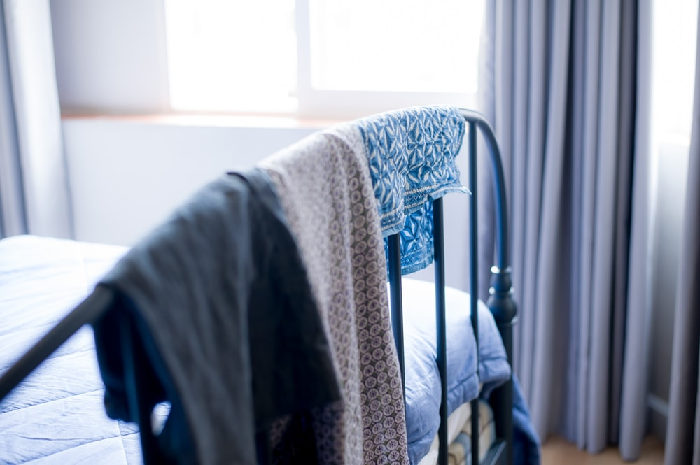 white and gray textile on blue steel bed frame