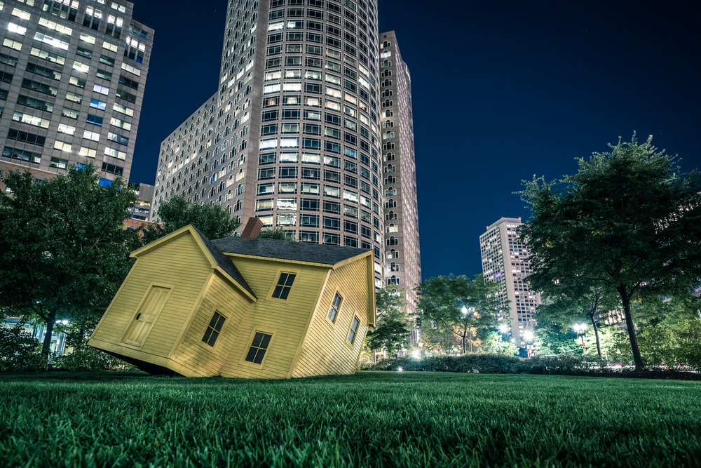 yellow house on green grass overlooking buildings at nighttime
