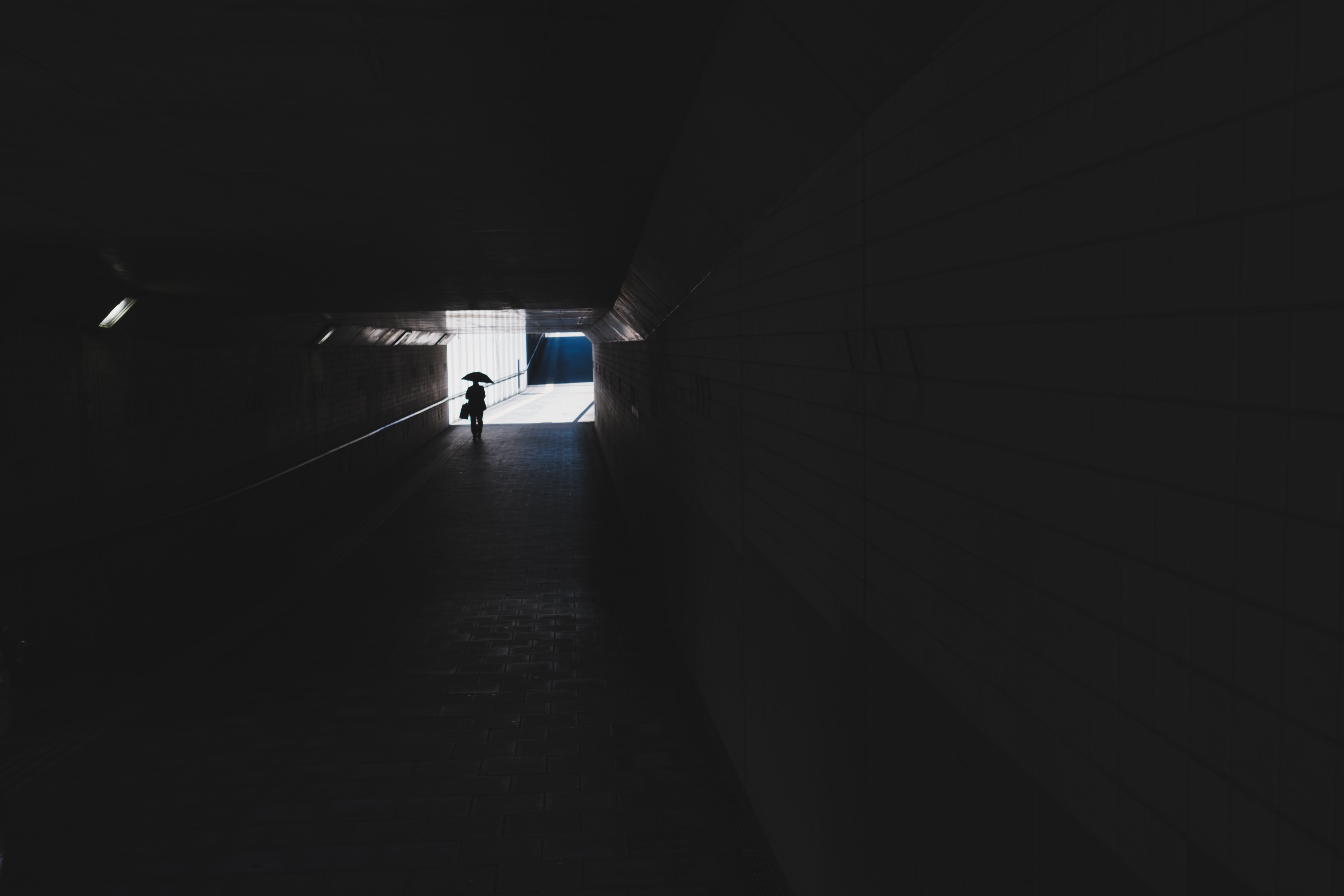 silhouette photo of person walking in tunnel