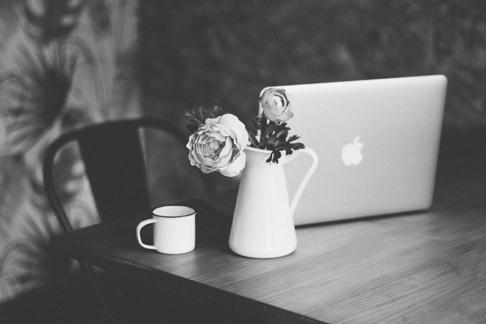 selective focus and grayscale photography of petaled flowers on vase beside cup and MacBook on table