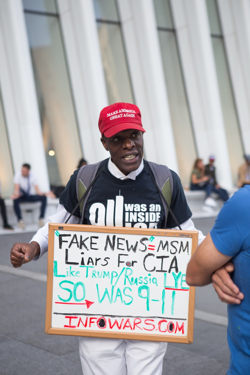 man in black and white shirt with red make America great again cap holding fake news=MSM sign near white building