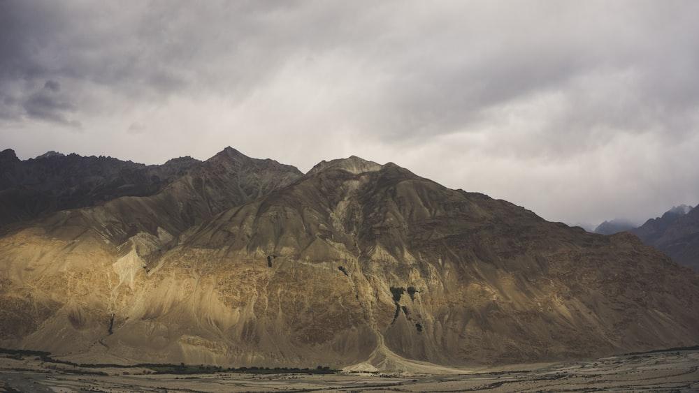 brown mountain near body of water