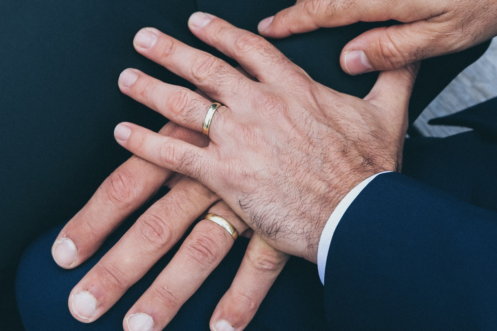 two man's hands wearing gold-colored wedding rings