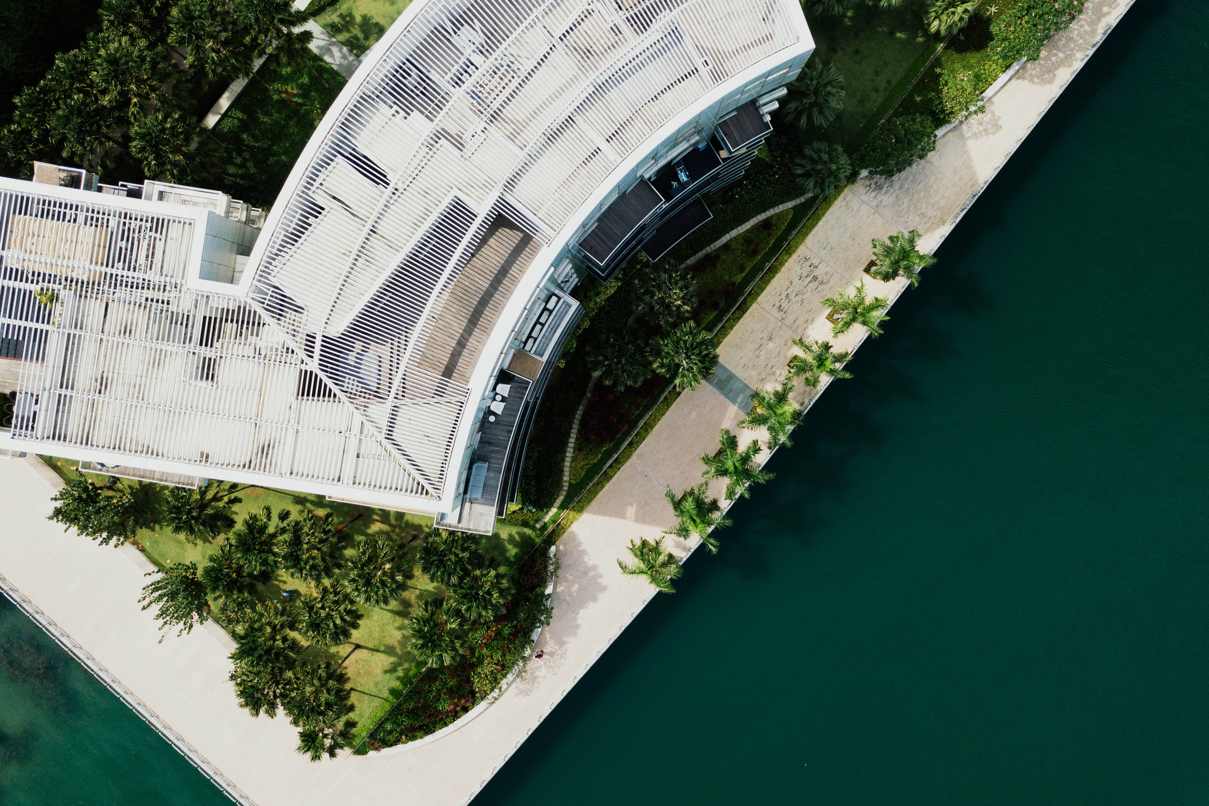 bird's eye view photography of a mid-rise building surrounded by trees near green body of water