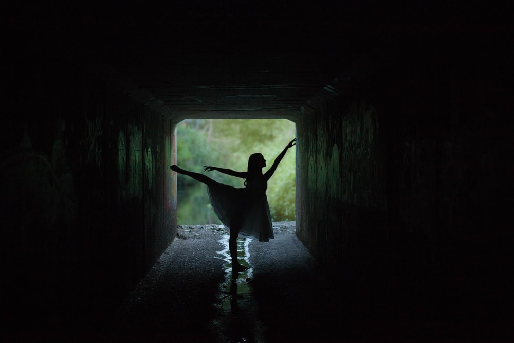 silhouette of woman doing ballet low light photography