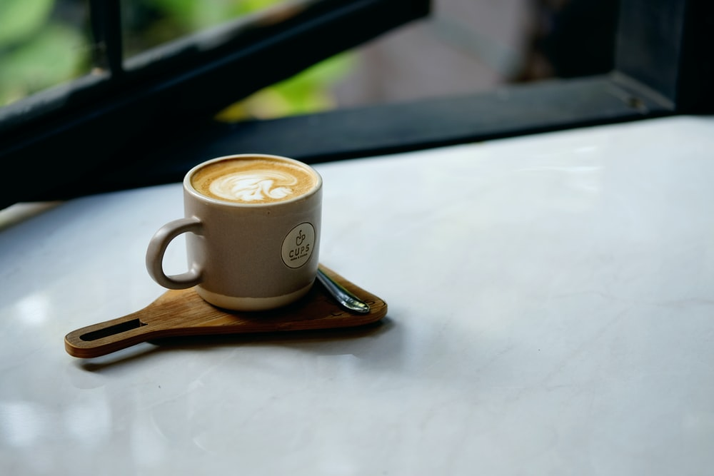 cup of coffee placed on beige wooden paddle with chrome spoon