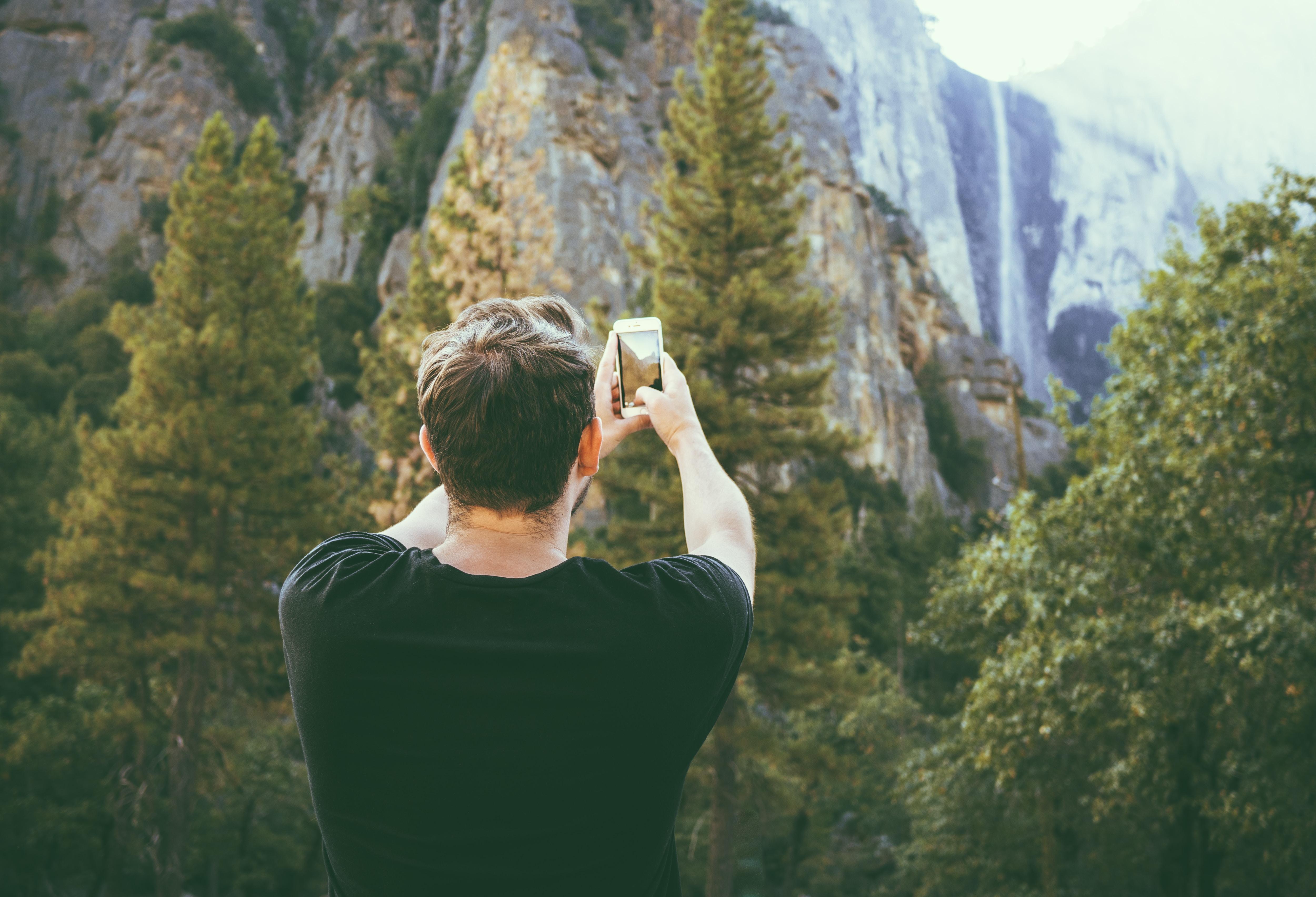 man taking photo of mountains