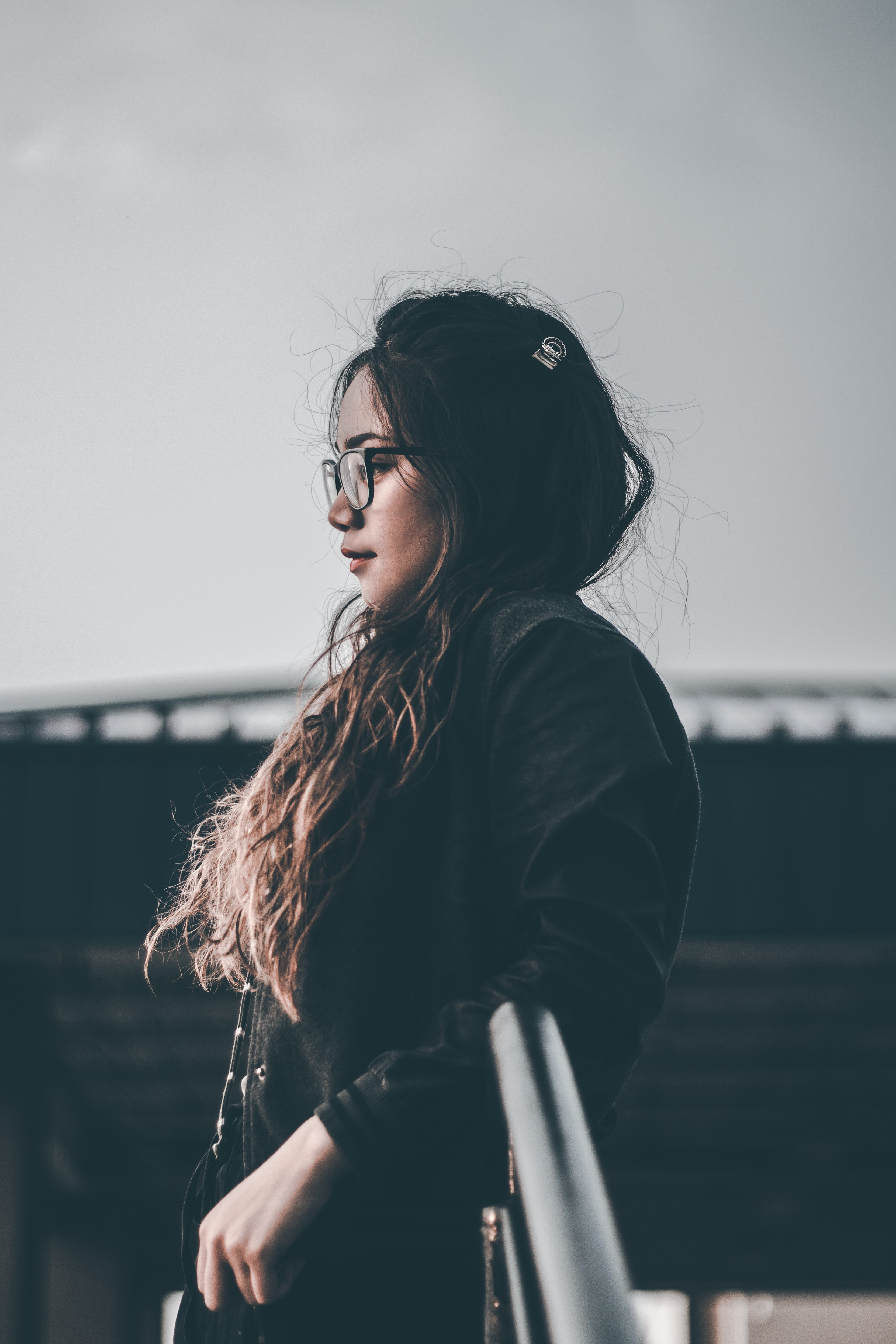 selective focus photography of woman standing beside railing