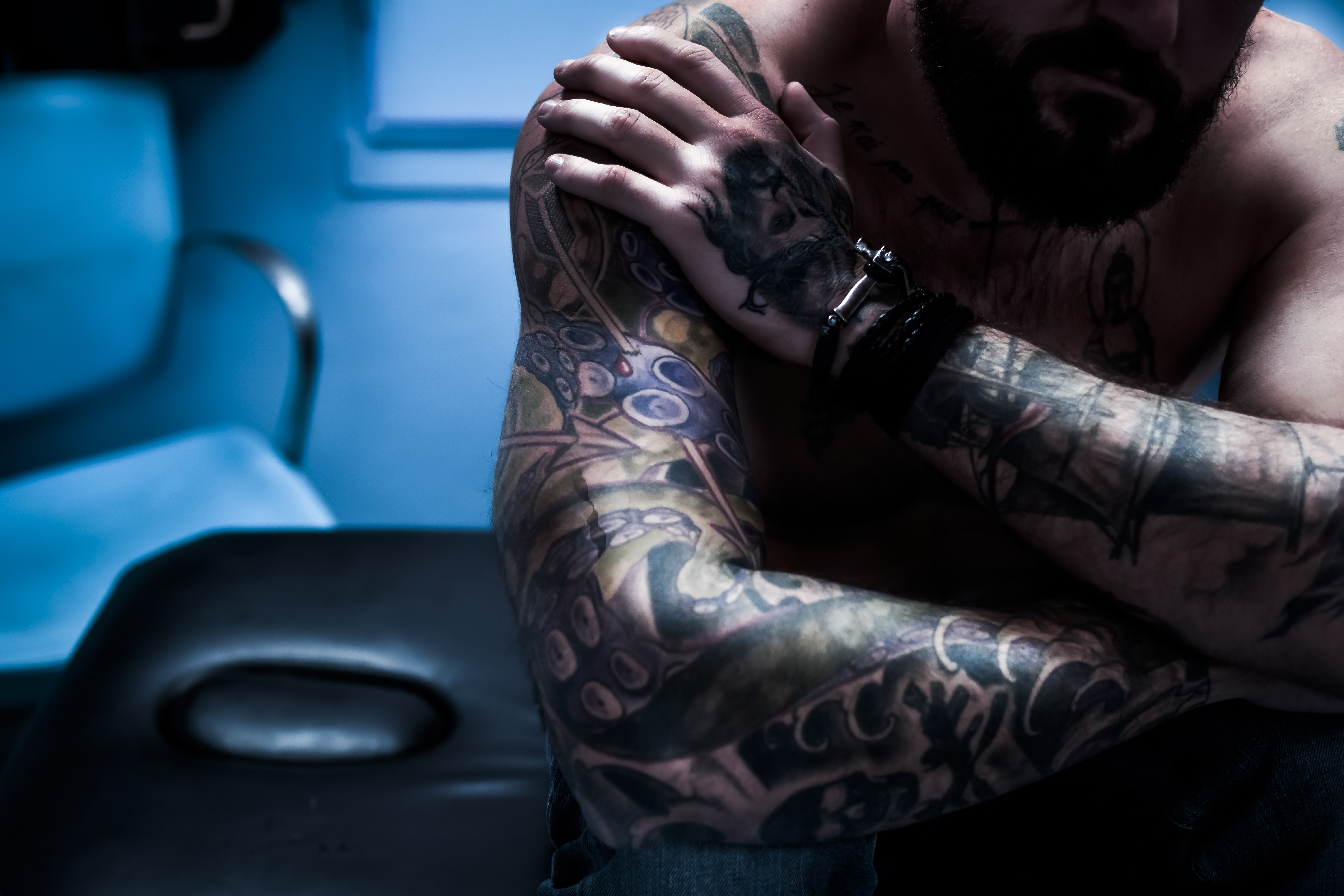 tattooed man holding his right shoulder