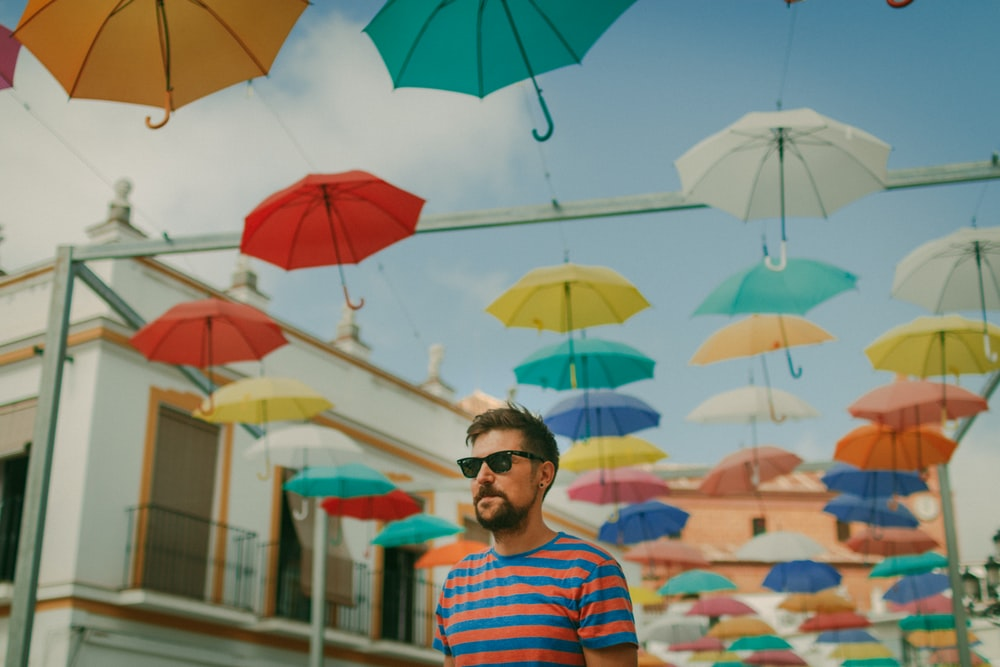 man wearing blue and red striped crew-neck t-shirt and black framed sunglasses