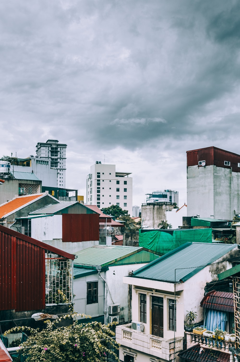white and gray concrete mid-rise buildings under gray clouds