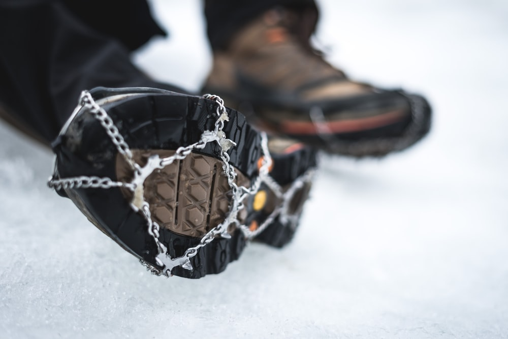 selective focus photography of black boot with snow chain