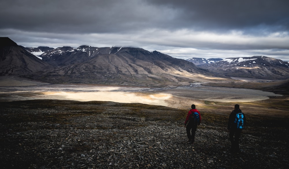 people walking across gray mountains under cloudy sky