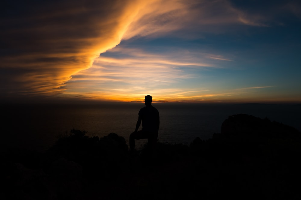 silhouette of person sitting on rock formation at golden hour